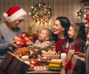 a mom with two girls on her lap as they sit at a Christmas dinner table, with a grandma giving a gift to one of the girls