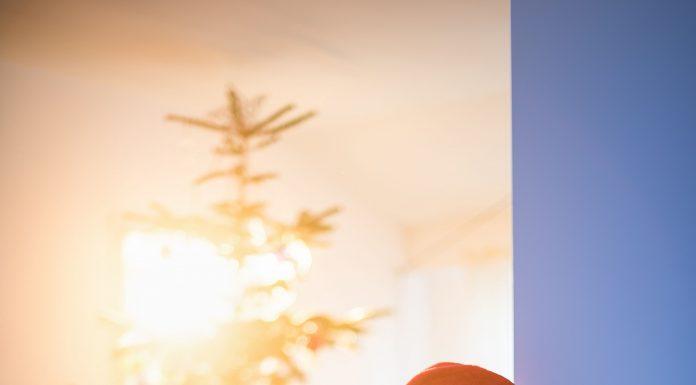 a young girl peeking around the corner at the Christmas tree on Christmas morning