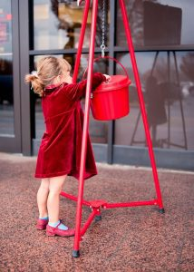 a little girl giving a donation in a Salvation Army pot