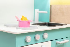 a close up of a mint green child's play kitchen