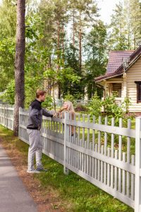 neighbors, a man and a woman, meeting over a white picket fence