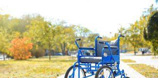 an empty wheelchair sitting on a park path