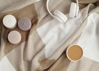 three scented candles, a pair of white headphones, and a cup of coffee on a tan and cream colored blanket