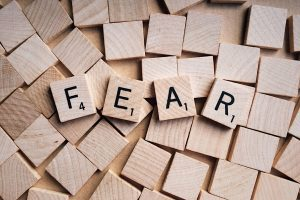 the word FEAR spelled out on scrabble tiles sitting atop a pile of blank tiles, representing an acronym to help you cope