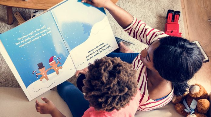 a mom and her son reading holiday books on the couch