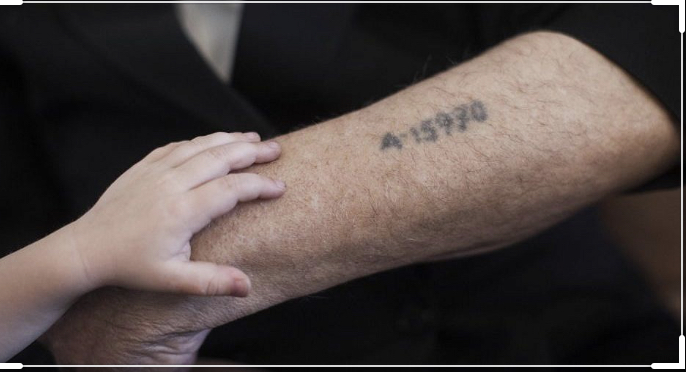 a close up of a holocaust tattoo on the arm of a survivor, with a child's hand resting on the arm