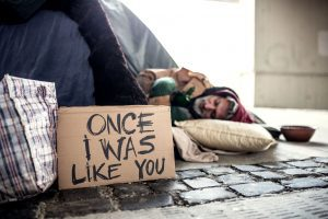 """a homeless man asleep on the street with a sign saying, """"once, I was like you."""""""