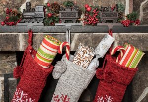 a close up of three stockings hanging on a stone mantle, filled with gifts from Santa