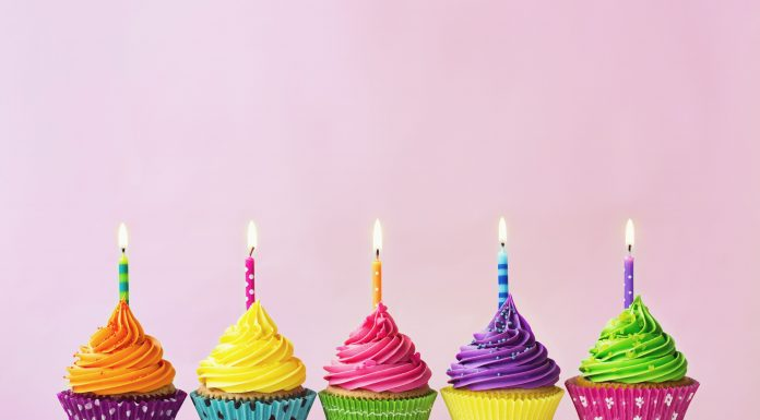 five birthday cupcakes with colorful wrappers and bright colored icing with lit candles on top against a pink background
