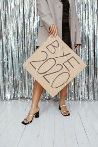 """a woman from the neck down, wearing a dress and heels, and holding a cardboard sign that says, """"Bye 2020"""""""