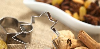 a silver christmas tree cookie cutter with walnuts and cinnamon sticks