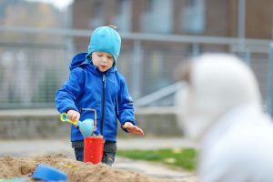a boy bundled up In a coat as he plays in a sandbox outside