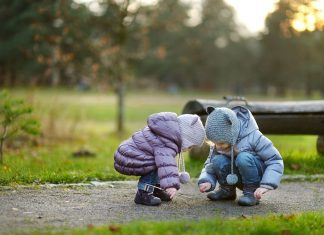 two little girls, bundled up in coats and hats as they squat down on a sidewalk to look at something on the ground
