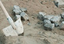 a shovel digging in dirt and finding rocks