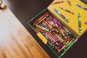 a box of crayons open on a tabletop ready to make crafts