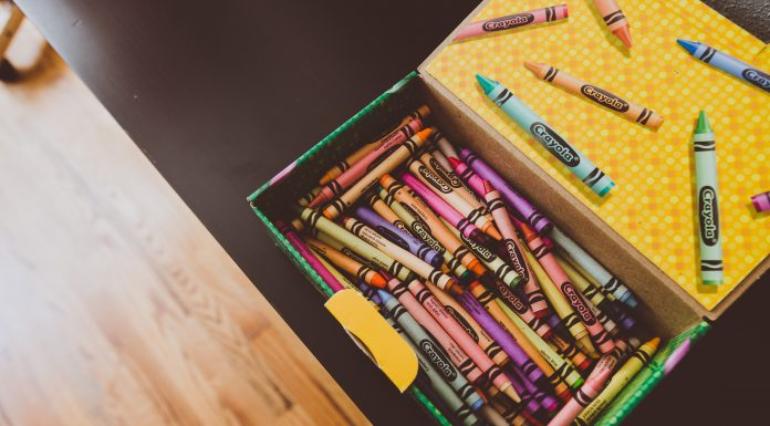 a box of crayons open on a tabletop