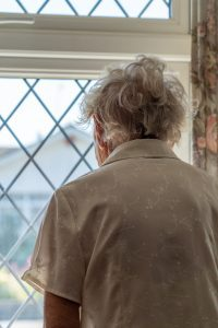 view from behind of an old woman looking out the window