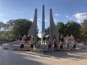a group of college students gathered in front of a fountain on Purdue's campus