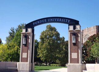 "an archway on a college campus with a sign saying, ""Purdue University"""