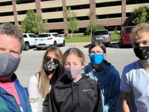 a mom and dad with their three kids, all wearing masks in a parking lot
