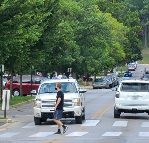 a teen boy walking in a crosswalk as he goes to college for the first time