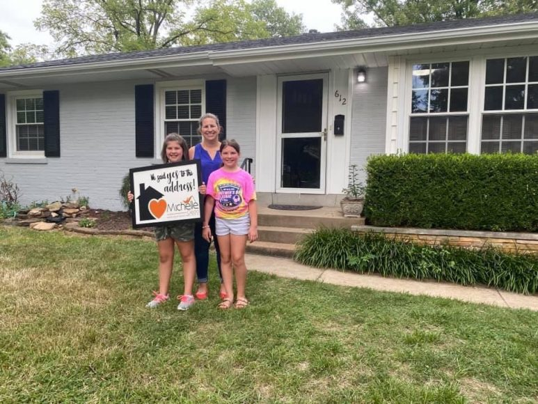 a mom and her two girls standing in front of their new house, holding a sign