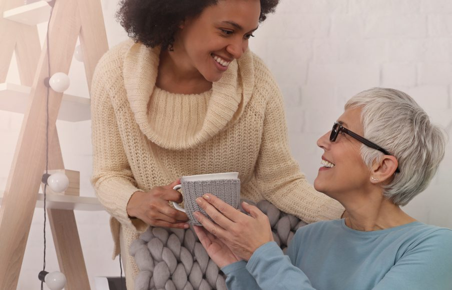 Kindness and care concept. Young female giving a cup of tea to older woman. Multi ethnic family