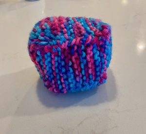 a 3D cube knitted from blue and pink yarn