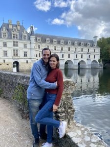 a couple standing in front of a historic castle in France