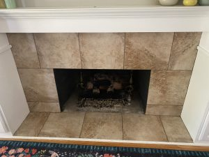 a fireplace with beige tile and a white mantle
