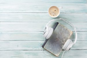 an old book with headphones on it next to a cup of coffee on a wooden slatted table