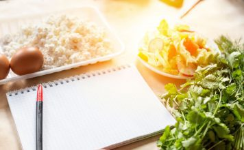 an empty notebook and pen on the counter surrounded by healthy foods for meal planning