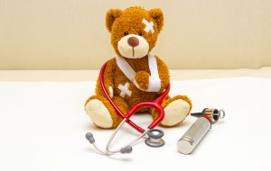 a teddy bear in a sling with bandages sitting on a doctor's table with a stethoscope
