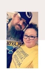 a man and a woman wearing St. Louis Blues t-shirts as they pose together for a picture