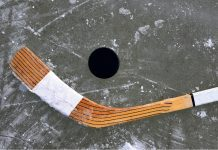 a hockey stick and puck on ice
