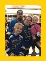 a mom, dad, and two little girls wearing St. Louis Blues hockey jerseys as they pose for a picture