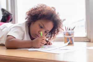 an African American toddler girl laying down and drawing by a window