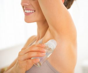 a close up of a woman in a tan tank top applying deodorant under her upstretched arm