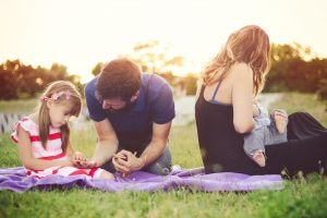 a family on a picnic blanket in the grass as the mom breastfeeds her baby