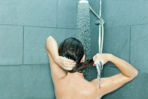 a woman standing in the shower, washing her hair
