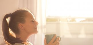 a woman sitting on a couch, eyes closed, inhaling the aroma from a steaming cup of coffee
