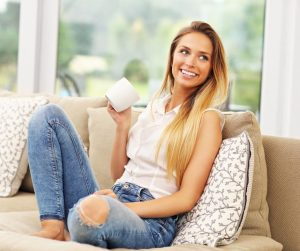 a woman sitting on a couch to enjoy a cup of coffee as she looks off into the distance
