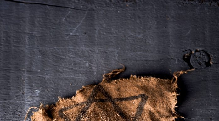 """a Jewish star badge and the Hebrew word for """"remember"""" on scraps laying on a wooden table"""