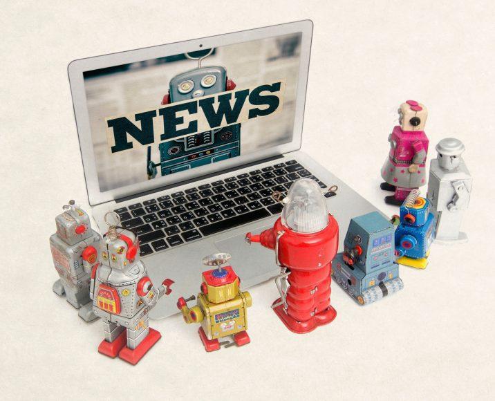 vintage robot toys gathered around laptop watching the news