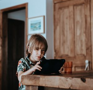 a child with medium length blonde hair sitting at a table while playing on a tablet during screen time