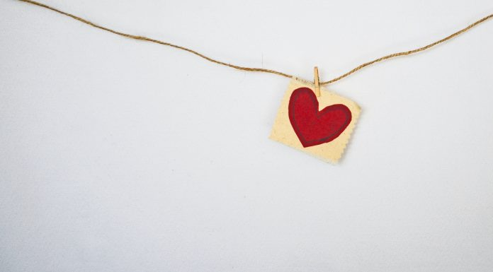 Valentine's Day heart painted on a piece of paper that is clotheslined to twine