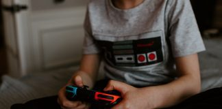 a person holding a Nintendo Switch controller in their hands