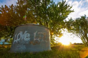 """graffiti on a metal cylinder that says, :Love Life"""" as the sun is setting behind it"""