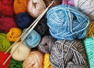 skeins of yarn in many colors along with a set of knitting needles