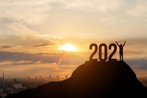 Large 2021 numbers silhouetted on a hilltop with the sun rising behind it and a person standing tall as the number 1